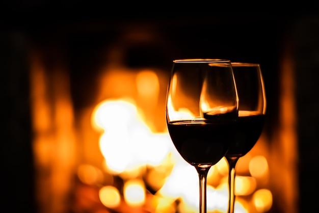 Duas taças de vinho tinto no fundo das luzes da lareira