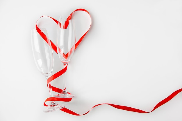 Duas taças de vinho vazias com uma fita vermelha dispostas em forma de um coração em um fundo branco