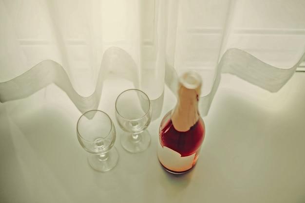 Duas taças de vinho vazias são colocadas ao lado de uma garrafa de vinho