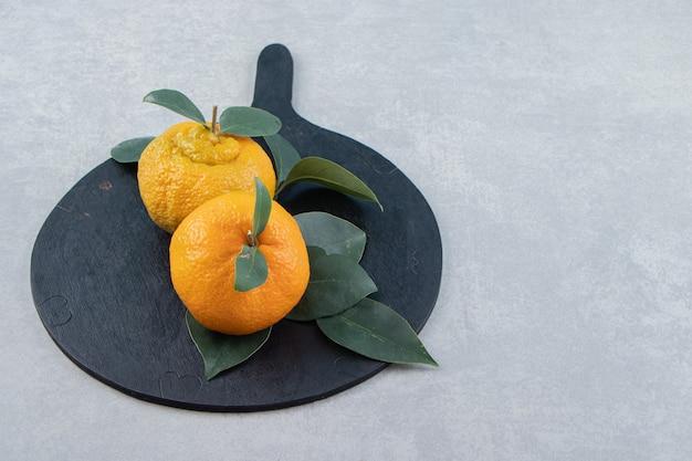 Duas tangerinas maduras com folhas na tábua de corte preta.