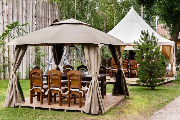 Duas tendas de lona com mesas e cadeiras de madeira.