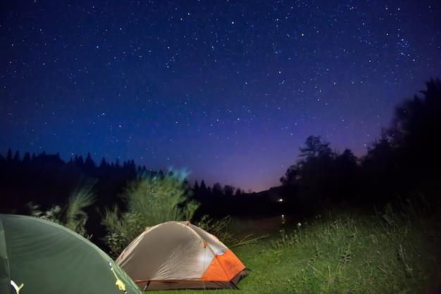 Duas tendas iluminadas nas montanhas sob um céu noturno escuro com muitas estrelas