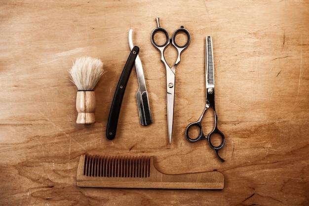 Duas tesouras, uma navalha perigosa, uma escova e um pente de madeira estão no meio em uma mesa de madeira. ferramenta de barbeiro em um fundo de madeira.