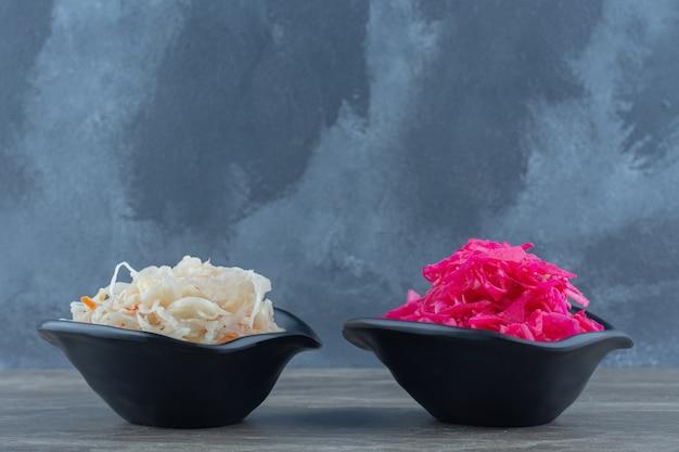 Duas tigelas cheias com repolho fermentado rosa e branco