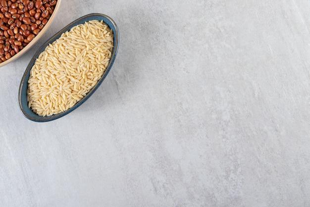 Duas tigelas cheias de arroz cru e feijão em fundo de pedra.