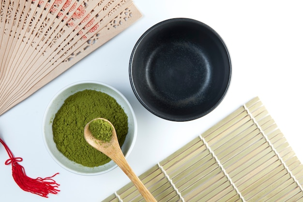 Duas tigelas de chá e uma colher de bambu com pó.