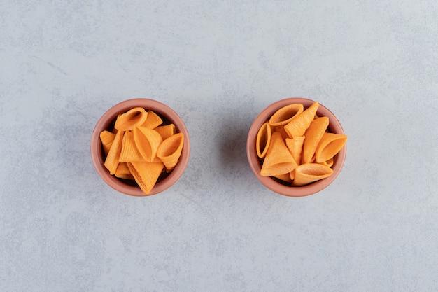 Duas tigelas de chips crocantes na pedra em forma de triângulo.