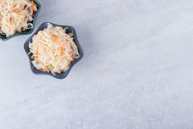 Duas tigelas de delicioso chucrute colocadas na mesa de pedra.
