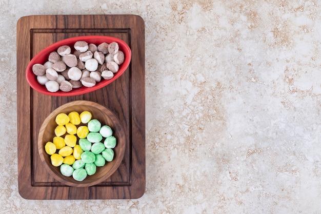 Duas tigelas de doces coloridos em uma placa de madeira
