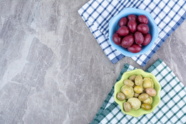 Duas tigelas de legumes em conserva e ameixas com toalhas de mesa.