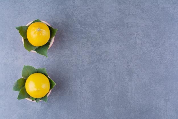Duas tigelas de limões maduros com folhas na mesa de mármore.