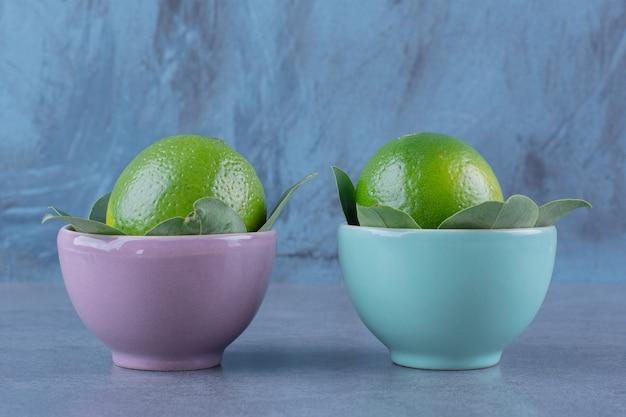 Duas tigelas de limões na mesa de mármore.