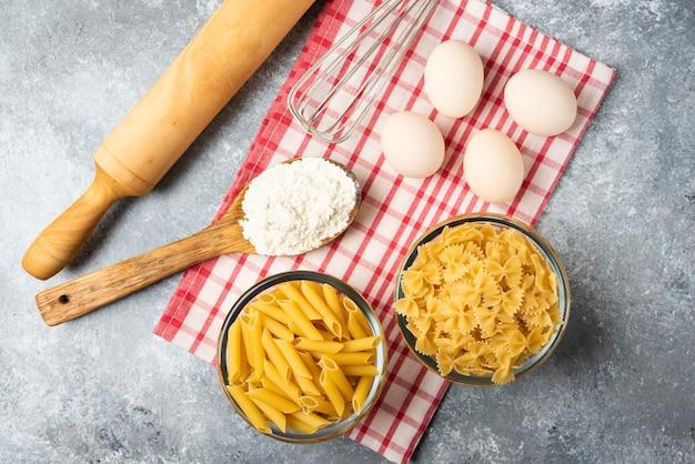 Duas tigelas de massa crua, ovos, colher de farinha e rolo na mesa de mármore com toalha de mesa.
