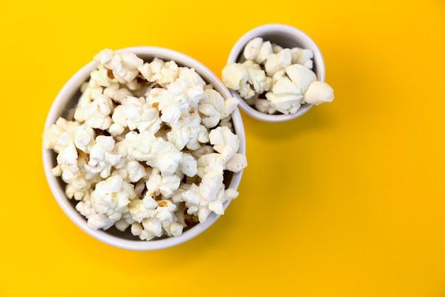 Duas tigelas de pipoca em um fundo amarelo. lanche para compartilhar. assista a séries ou filmes com amigos ou família.