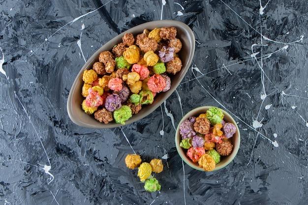 Duas tigelas de saborosas pipocas coloridas na superfície de mármore.