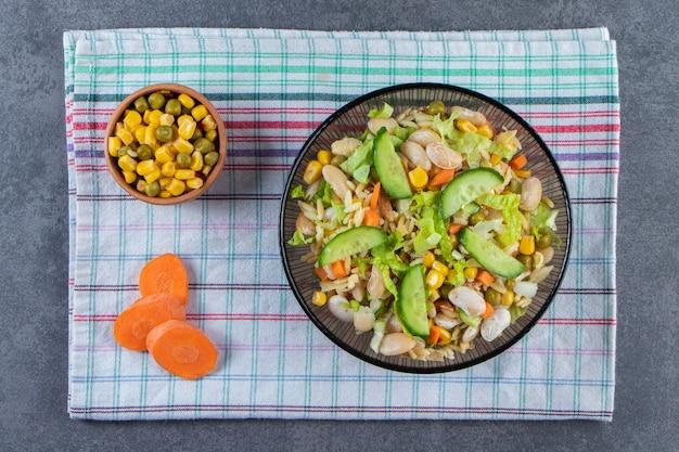 Duas tigelas de salada de legumes e cenoura fatiada em um pano de prato, na superfície de mármore.