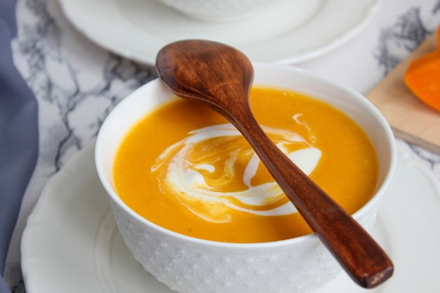 Duas tigelas de sopa de abóbora no branco com tecido cinza e fatias de abóbora