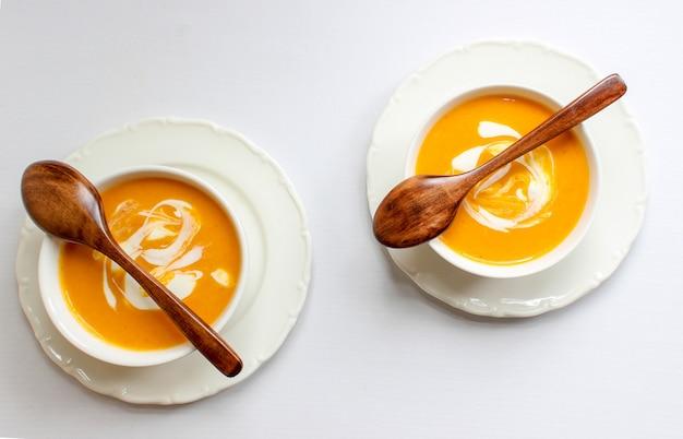 Duas tigelas de sopa de abóbora no fundo branco com tecido cinza e fatias de abóbora
