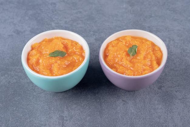 Duas tigelas de sopa de lentilhas, na superfície de mármore.
