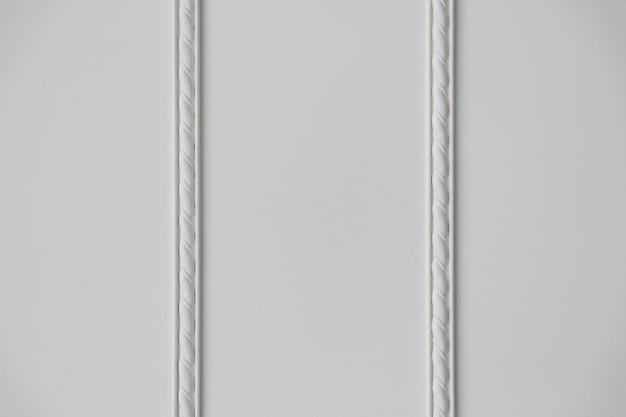 Duas tiras de moldura de estuque em relevo na parede branca, close-up