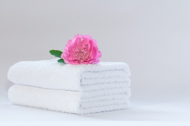 Duas toalhas de terry dobradas ordenadamente brancas com uma flor de rosa