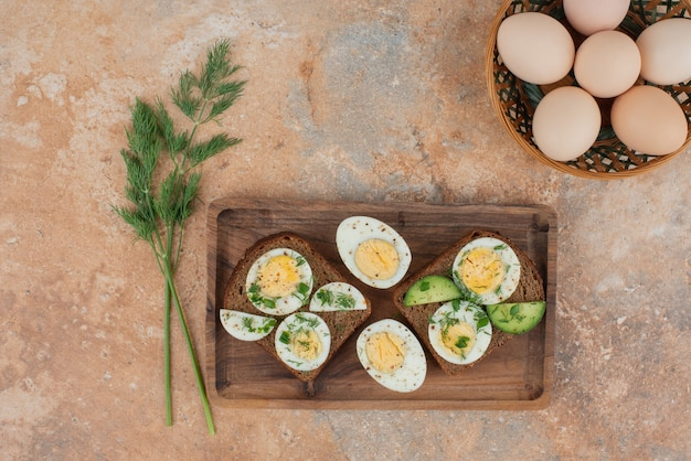 Duas torradas com pepino e ovos cozidos na superfície de mármore