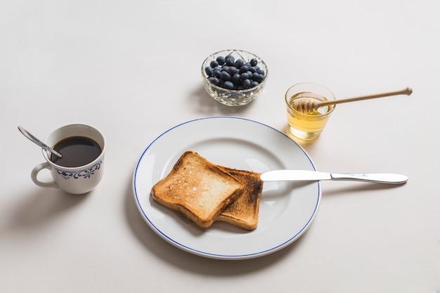 Duas torradas de pão com mel; chá e mirtilos em fundo branco