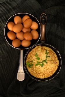 Duas torrefadoras em direções opostas com ovos frescos e uma omelete dividida em quatro partes