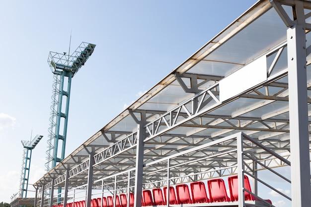 Duas torres de relógio um pouco enferrujadas de metal no estádio de esporte contra o céu claro