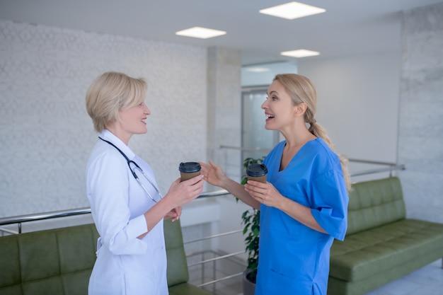 Duas trabalhadoras médicas tomando café, conversando