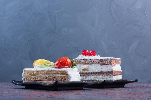 Duas travessas com fatias de bolo na mesa abstrata.