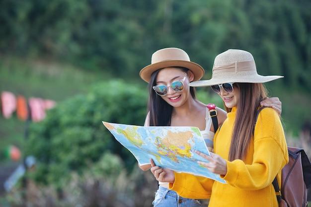 Duas turistas do sexo feminino segurar um mapa para encontrar lugares.