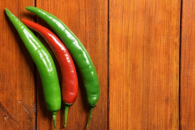 Duas vagens verdes e uma vermelha fresca de pimenta chili estão à esquerda em uma mesa de madeira marrom