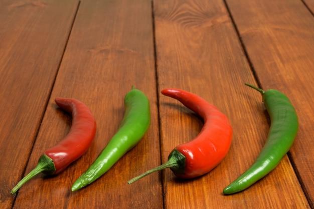 Duas vagens vermelhas e duas verdes de pimenta fresca sobre uma mesa de madeira marrom em primeiro plano