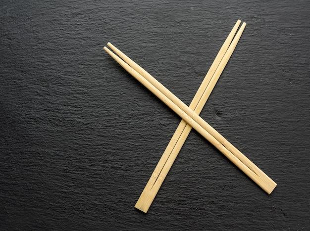 Duas varas de madeira para sushi em um fundo preto, vista superior