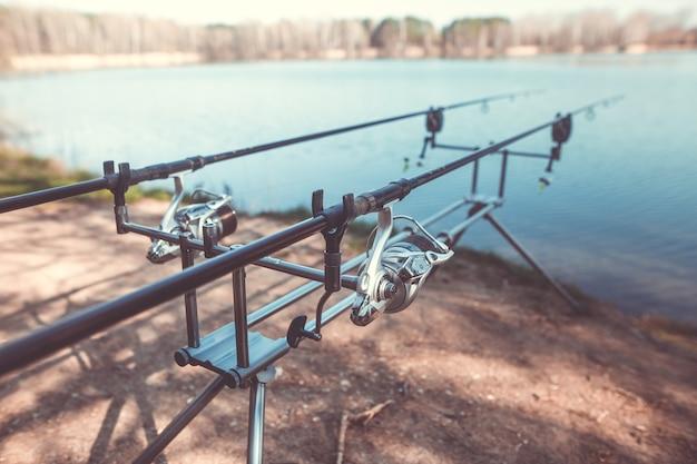 Duas varas de pesca fundidas na prateleira à beira do lago, prontas para pescar, pescar, pescar, conceito de esporte