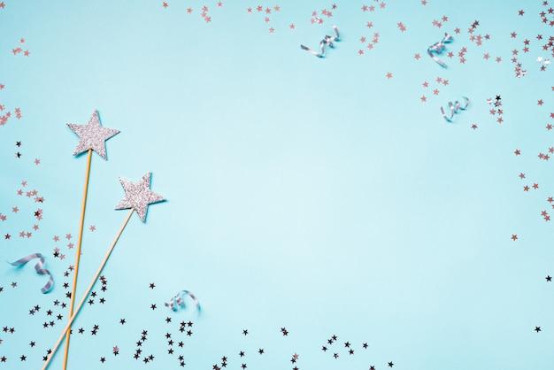 Duas varinhas mágicas de festa de prata, lantejoulas e fitas sobre um fundo azul. copie o espaço.