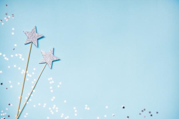 Duas varinhas mágicas de prata e lantejoulas espalhadas sobre um fundo azul. copie o espaço.