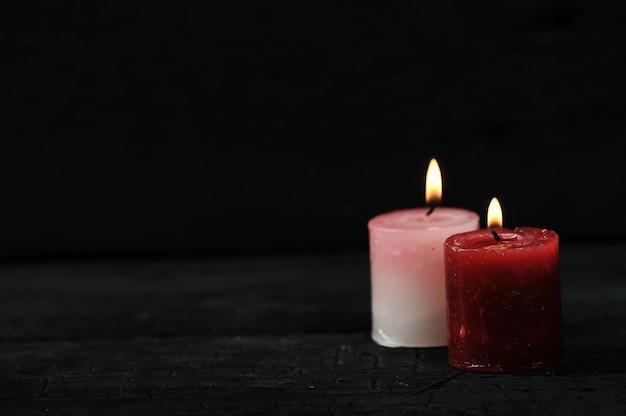 Duas velas com fogo aceso em fundo preto