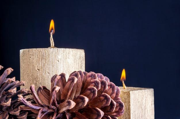 Duas velas douradas queimando com pinhas