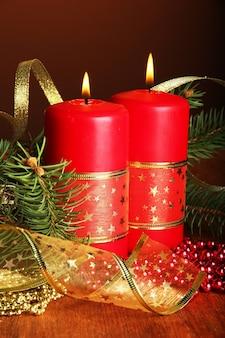 Duas velas e enfeites de natal, em fundo marrom