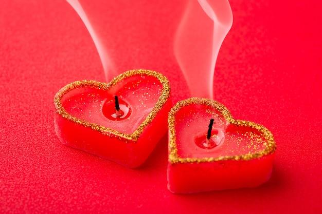 Duas velas em forma de coração com fogo apagado