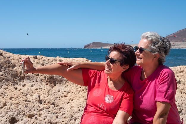 Duas velhas amigas sentadas em um banco olham para o celular e tiram uma selfie. conceito de vínculo e amizade. montanha e mar atrás deles. paraíso para os amantes do surf