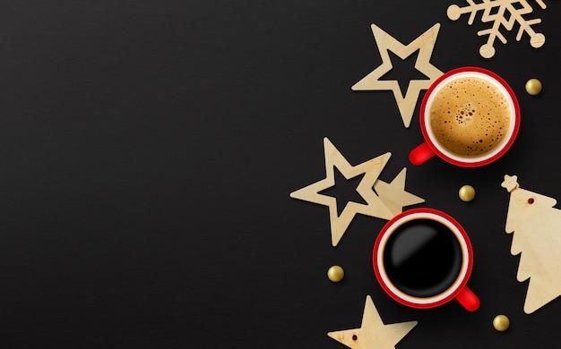 Duas xícara de café vermelha e decoração de natal em fundo preto papel
