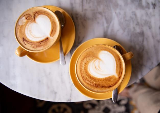 Duas xícaras amarelas de cappuccino quente no fundo da mesa de mármore