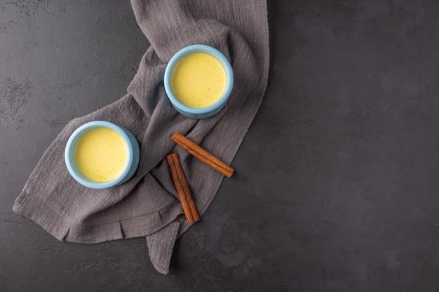 Duas xícaras azuis com o tradicional chá indiano masala chai e paus de canela em um guardanapo de linho