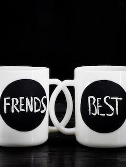 Duas xícaras brancas com a inscrição de pé em uma madeira preta, conceito de férias
