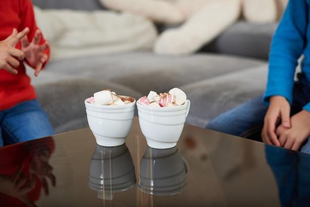 Duas xícaras brancas com chocolate e marshmellows em uma mesa de vidro transparente no fundo de duas crianças sentadas ao redor da mesa