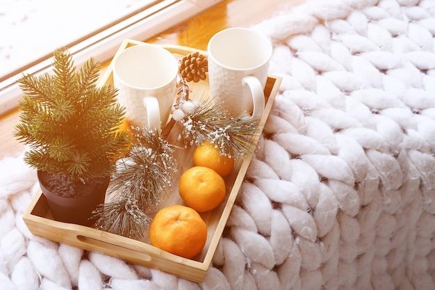 Duas xícaras brancas com decorações festivas, tangerinas, cones de pinheiro, abeto e ramos de pinheiro ...