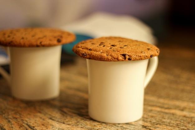 Duas xícaras brancas de biscoitos de aveia com gotas de chocolate